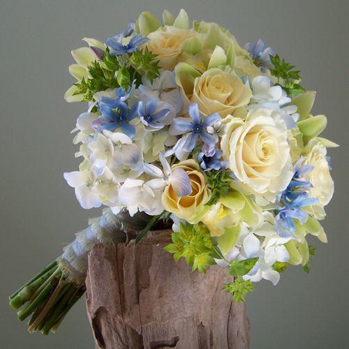 bridesmaid bouquet with tweedia, pale blue hydrangea, Cream Prophyta roses, green mini cymbidiums, and bupleurum