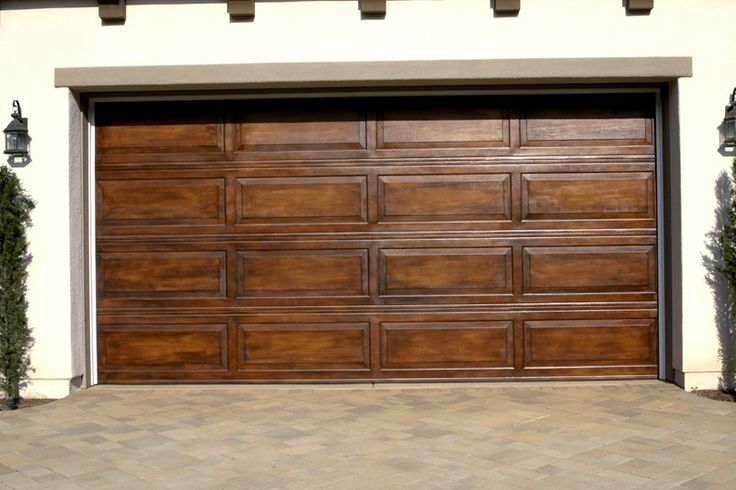 Have your garage door faux finished to simulate wood.!  Yes, most of these photos are standard  metal garage doors that we have faux finished to look like wood.  Wood graining, and layering stains achieve a deep rich  wood look our faux garage doors are durable and protected against elements.  They do not fade as regular painted garage doors do.