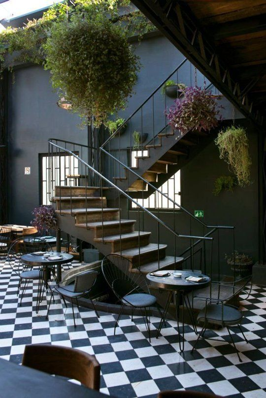 A dark-walled restaurant in Mexico City - love the pop of greenery to enliven the space and the graphic pop of the checkerboard floor laid on the diagonal.