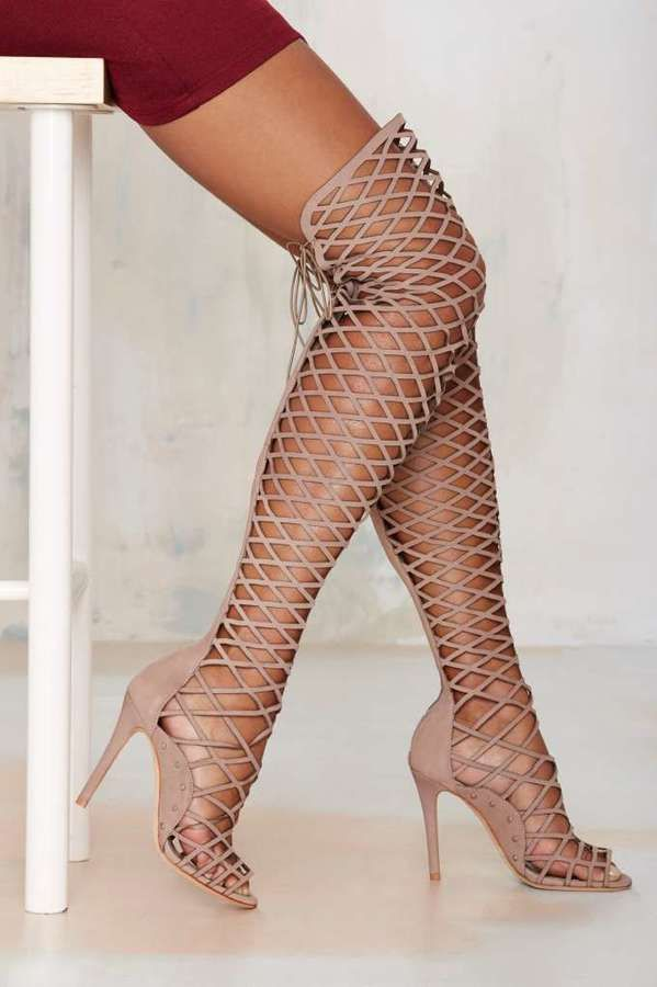 Get caged in all the right ways. The Karlyanna Heel and made in beige leather and feature a caged design, knee-high silhouette, peep toe, and zip and lace-up closure at back. Wear it with a long-sleeved mini dress and leather envelope clutch. by Schutz.