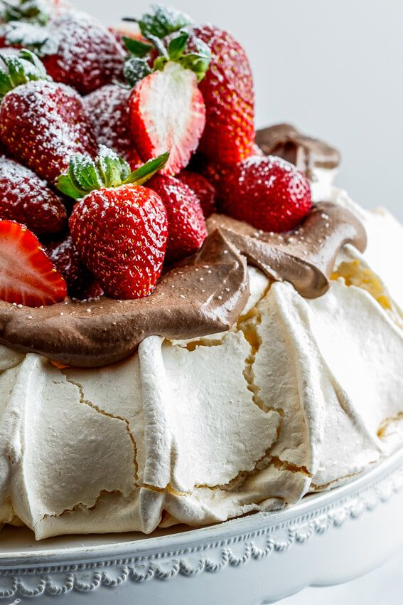 Perfectly marshmallowy pavlova topped with luscious chocolate cream and a mountain of fresh strawberries makes an easy yet impressive dessert. Click for recipe. simply-delicious-food.com