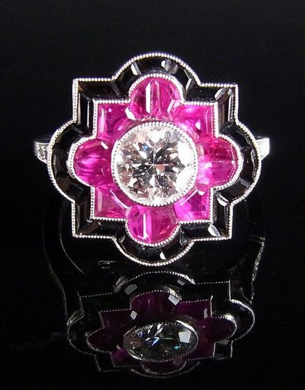 Platinum Art Deco diamond, ruby and onyx ring. The central, round brilliant cut, millegrain set diamond weighing 0.74 ct and of high colour and clarity bordered by twelve mixed cut rubies and twenty mixed cut onyxes to an extremely fine open work mount and diamond set shoulders.