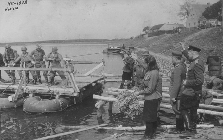 Александр Устинов-Встреча на Эльбе. Советские военнослужащие на берегу реки встречают прибывающих американцев. На фото американские солдаты (слева на право): Боб Хааг (Bob Haag), Эд Руфф (Ed Ruff), Карл Робинсон (Carl Robinson) и Байрон Шивер (Byron Shiver).