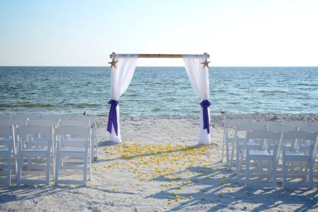 Bamboo style beach wedding arbor draped with white fabric and purple sashes, complete with a rose petal aisle