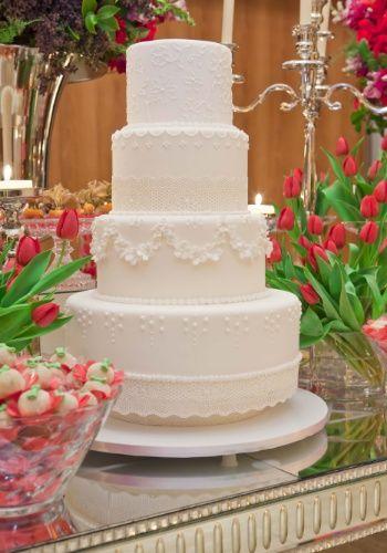 Bolo de quatro andares com textura de renda e decorado por flores de açúcar