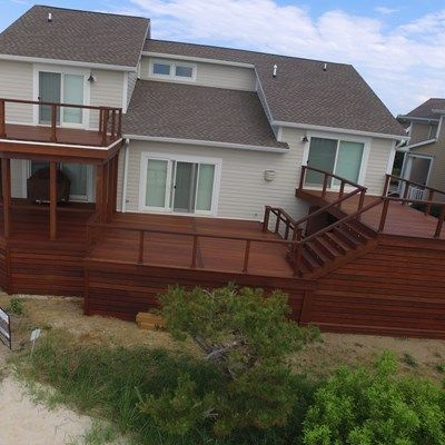 "We built a 1400 square foot multi level IPE deck complete with 1200 square feet of IPE skirting and a 200 square foot IPE walkway. All decking was 5/4""x5.5"".  All railing was complete with IPE members and stainless steel 3/16"" cable.  We also installed tongue and groove IPE boards on the ceiling of the porch. All lighting was done using LED riser lights and LED down lights on selected rail posts.  We also built custom barn style doors at the entrance into the deck and into the shower area…"