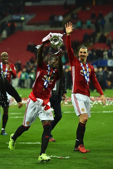 Manchester United's Ivorian defender Eric Bailly celebrates with the trophy on the pitch after their victory in the English League Cup final football...
