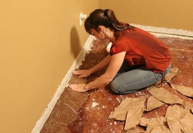 Tagelang klebt die Frau Papier auf den Boden. Am Ende hat sie richtig gespart.