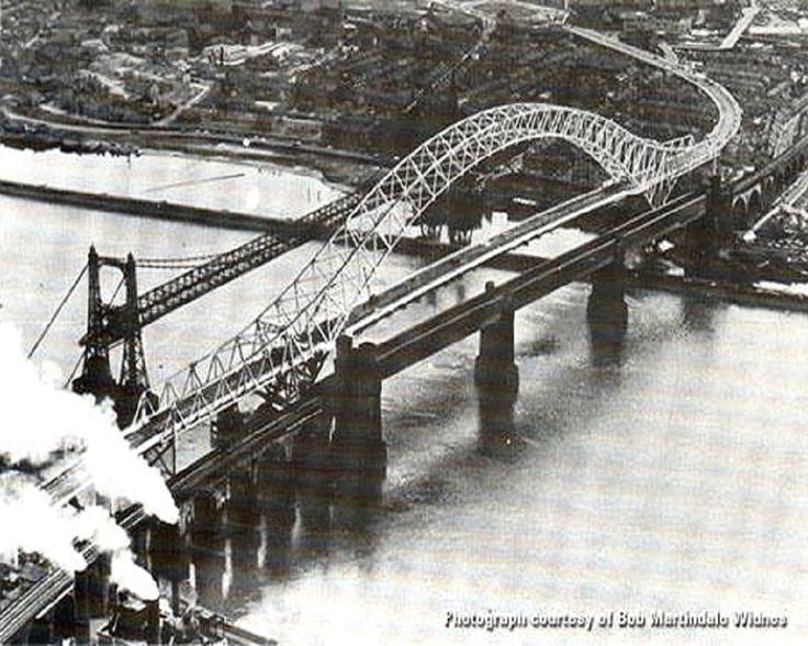 The Silver Jubilee Bridge crosses the River Mersey and the Manchester Ship Canal between Runcorn and Widnes in north west England.    It was opened in 1961 as a replacement for the Widnes-Runcorn Transporter Bridge, and was initially known simply as the Runcorn Bridge or Runcorn–Widnes Bridge.     In 1975–77 it was widened, after which it was given its official name in honour of the Queen's Silver Jubilee.     The bridge has been designated by English Heritage as a Grade II listed structure.