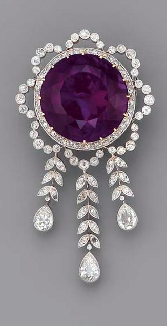 A BELLE EPOQUE AMETHYST AND DIAMOND BROOCH The circular-cut amethyst within the diamond garland surround, suspending a graduated fringe of diamond leaves to the three pear-shaped drops, millegrain setting, mounted in platinum and gold, circa 1900