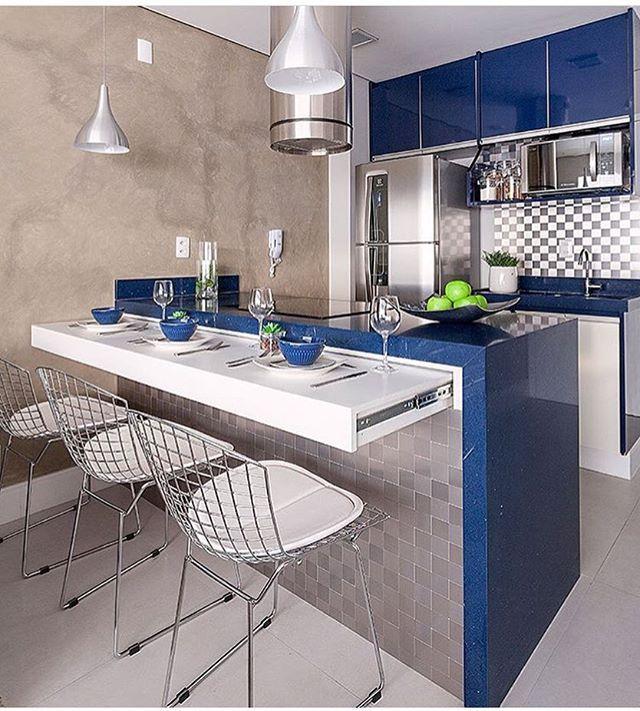 Cozinha integrada com marcenaria azul. Destaque para o balcão retrátil na…