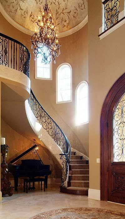 This staircase off the Foyer is so elegant.The windows as the stairs ascend,the chandelier & rounded wood entry door make an exquisite combination.