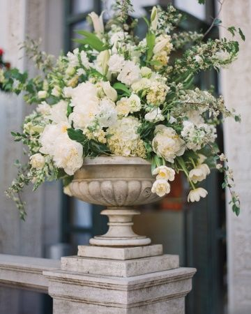 Peonies, variegated bush ivy, and double tulips sprout from grand stone urns