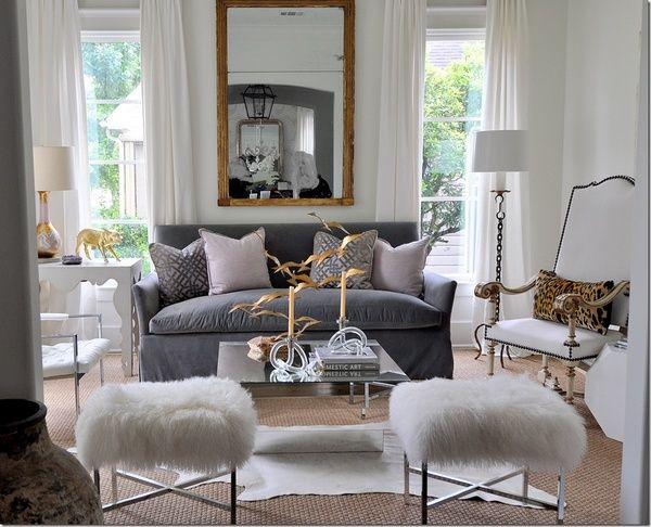 Gorgeous all white living except for the gray sofa & pillows.  The furry ottomans are so fun! via The Decorista