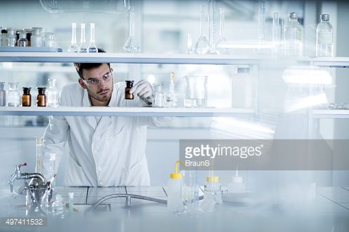 Stock Photo : Young chemist choosing the right bottle in a laboratory.