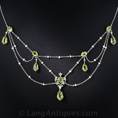 Edwardian Peridot, Diamond, and Pearl Necklace. From the first or second decade of the last century, a ravishing and romantic, English-made swag necklace composed of five pairs of gleaming lime green peridots, the center of which is enveloped in an open foliate design, artfully rendered in platinum, sparkling old mine-cut diamonds and a small lustrous natural pearl. The platinum swags are punctuated with small natural pearls. A truly exquisite and feminine, original Edwardian jewel