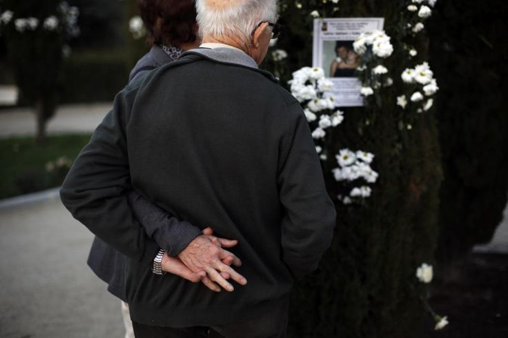"""A couple holds hands as they look at the image of a young couple who were killed in the Madrid train bombings at the """"Forest of the Remembrance"""" (El Bosque del Recuerdo), a memorial garden which commemorates the victims of the 2004 Madrid train bombings, in Madrid, Spain, March 11, 2015. REUTERS/Susana Vera"""
