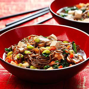 """Instead of high-sodium packaged ramen for lunch, try healthy soba -- buckwheat noodles -- with a protein-packed vegetarian saute. Because mushrooms tend to soak up so much oil, they are """"sweated"""" in a covered pan so that they soften in their own juices. While tofu is the traditional protein in this Japanese dish, you can substitute leftover cubed chicken or turkey for the tofu, and peas for the edamame, if you like."""