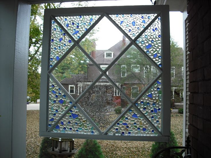 Dress up an old salvaged window with inexpensive decorative glass stones to create a stunning garden decoration! via Dollar Store Crafts