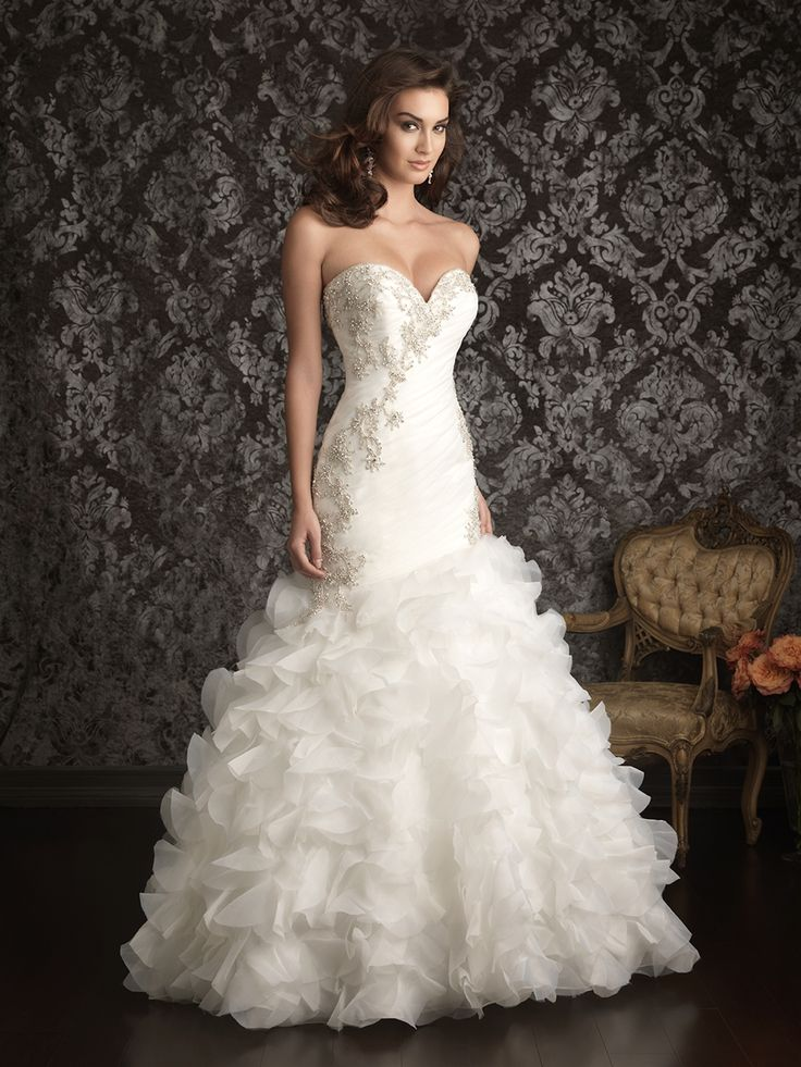 This fit and flare gown is constructed from soft organza. The fitted, strapless bodice features a sweetheart neckline ruched asymmetrically with embroidery with Swarovski crystals accents. ALLURE 9012