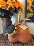 This cute sunflower pumpkin has a wood twig stem and corn husk leaves. 9h x 7h