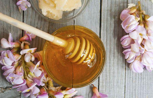 A jar of acacia honey on a wooden table, next to acacia blossoms