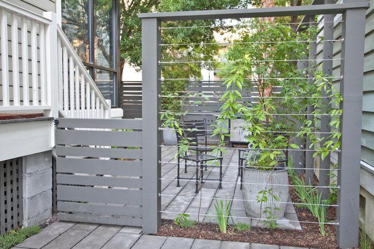 Une clôture vient délimiter l'espace privé de bien belle façon. Des câbles fixés entre les poteaux accueilleront des plantes grimpantes au fil du temps. Ceci assurera au patio toute l'intimité nécessaire. Modern Landscape by REMARK (Houzz)