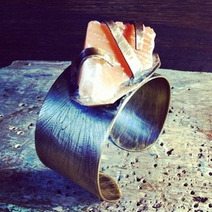 This is my Topanga bracelet. It's a brass cuff with bronze settings and an red Mexican calcite rock.