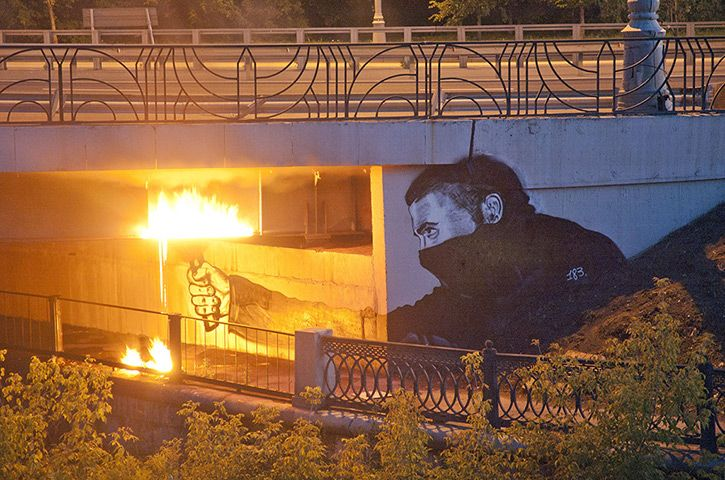 Instigators of Bridges depicts a rioter with a flare painted on a flyover. At night, flames are lit in the work  (street art of P183)
