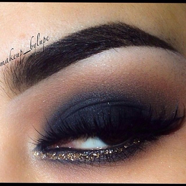 Dramatic smokey eyes with gold glitter lining the bottom lash line
