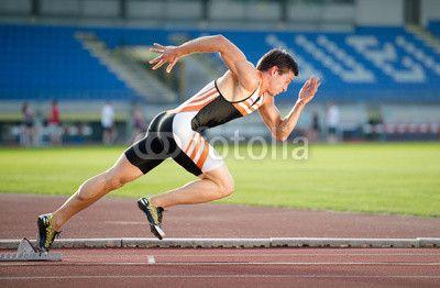 Sprinter leaving starting blocks on the running track. Explosive