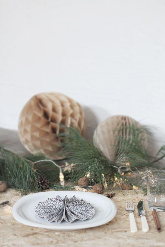 Christmas table setting idea: walnuts, a lighting garland, pom poms, pine twigs.