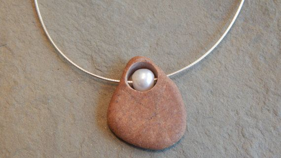 Beautiful beach stone that I drilled a large hole into and placed a beautiful white freshwater pearl in the middle of -- all of it is held