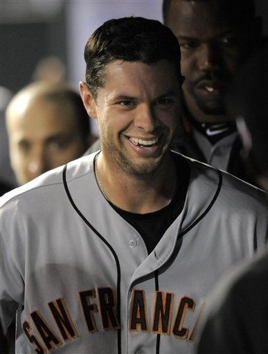 San Francisco Giants' Brandon Belt smiles as he is congratulated by teammates after hitting a solo home run against the Colorado Rockies during the seventh inning of a baseball game Tuesday, Sept. 11, 2012