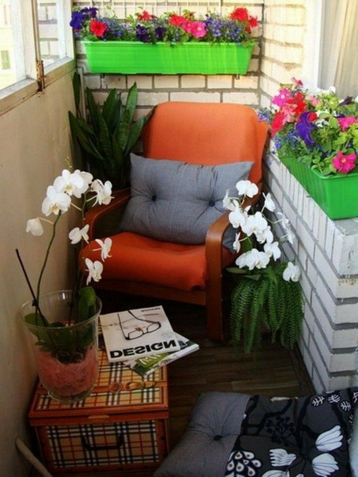 red chair with grey cushion, to bright green planters with colorful flowers, box in plaid serving as table, with potted orchid and magazines, porch ideas
