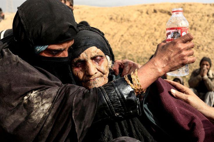 """Dos mujeres desplazadas que han huido de sus hogares descansan en el desierto mientras esperan a ser llevadas a un campo de refugiados, el 27 de febrero de 2017. Zohra Bensemra es la autora de la fotografía. """"Tomé esta imagen de Khatla Ali Abdallah, una mujer de 90 años de edad, después de que huyese de Mosul. Sus ojos estaban rojos por la fatiga, estaba tan agotada que no se podía levantar ni sentar bien. Me miró como si no hubiese comido ni bebido en mucho tiempo. El momento fue tan…"""