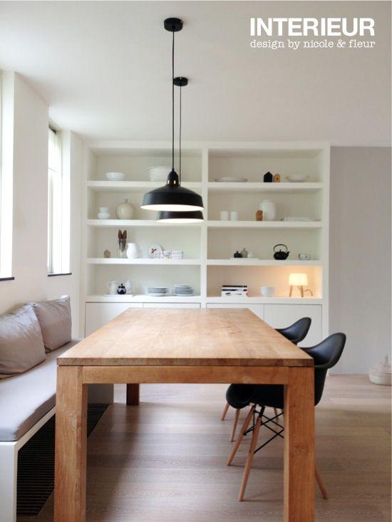 Dit huis van binnen heeft een grote houten rechte, lange tafel, Met een grijzige bank en twee zwarte stoelen. Boven de tafel hangen twee zwarte lampen, Vlakbij de tafel staat een grote witte open kast met allemaal spulletjes erin