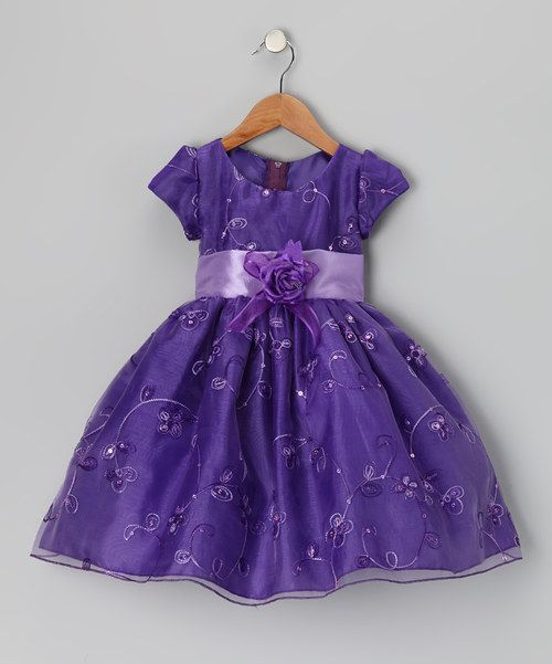 Sporting darling details and lots of twirlability, this dress pulls out all the stops with an angelic sheen, full skirt and satin waist sash. The half zipper on the back allows for fuss-free dressing and changing.