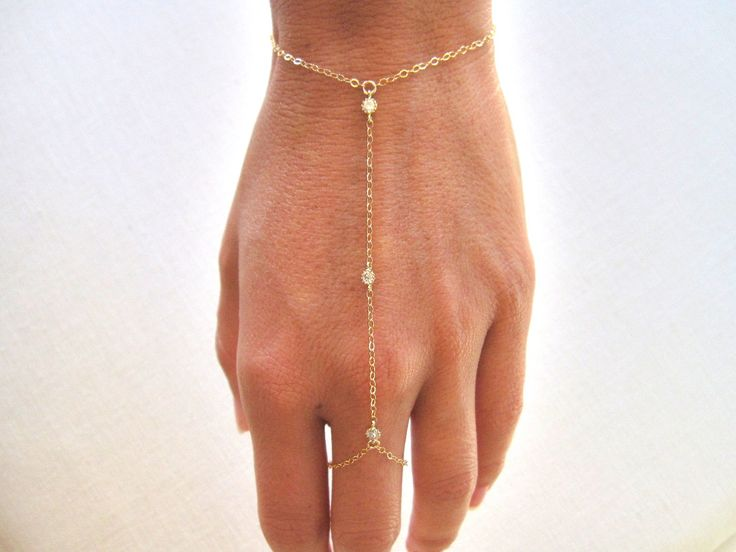 slave bracelet - hand chain // delicate 14k gold filled chain and 3 tiny cz cubic zirconia diamonds ring bracelet. $86.00, via Etsy.
