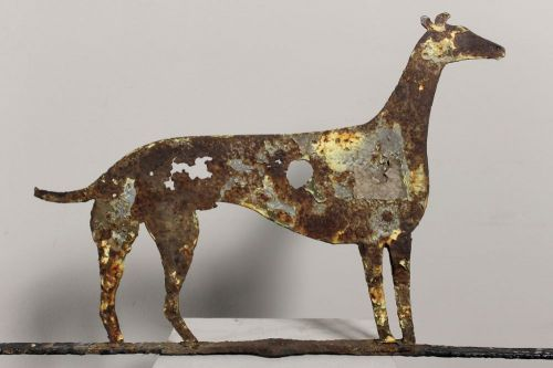 A large rare and totally original naive early 19th century iron weathervane of a greyhound,retaining traces of several layers of weathered paint and original riveted joints.