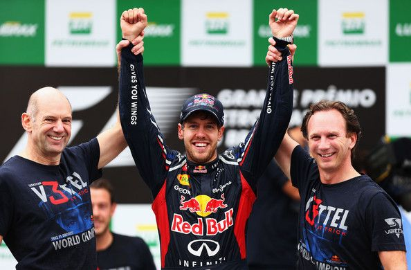 Sebastian Vettel (C) of Germany and Red Bull Racing celebrates with Red Bull Racing Chief Technical Officer Adrian Newey (L) and Team Principal Christian Horner (R) on the podium as he finishes in sixth position and clinches his third consecutive drivers world championship during the Brazilian Formula One Grand Prix