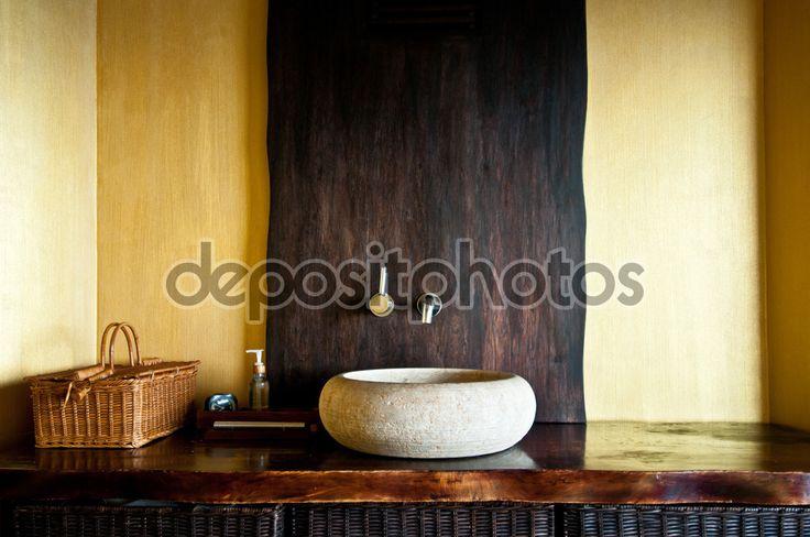 Moderní koupelny interiér s původní bílé kamenné umyvadlo, hodiny, dřevěné koše a dávkovač mýdla. Dřevěný interiér lázní v žluté a zlaté barvy. Selektivní pozornost, jen součástí koupelny je v kostce