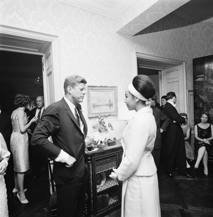 President John F. Kennedy visits with actor and singer, Diahann Carroll, during an evening reception at the residence of Arthur B. Krim and Dr. Mathilde Krim in New York City, New York. Eunice Kennedy Shriver stands at far left in background. Cecil Stoughton. White House Photographs. John F. Kennedy Presidential Library and Museum, Boston