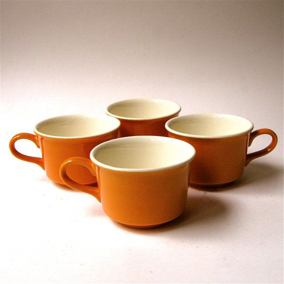 Great set of Mid Century pumpkin orange mugs from the 1960s-1970s. This set consists of four ceramic coffee mugs with a warm pumpkin orange
