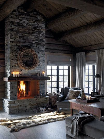 Living room with dark wood floors and ceiling, dry stacked stone fireplace, and a fur rug.