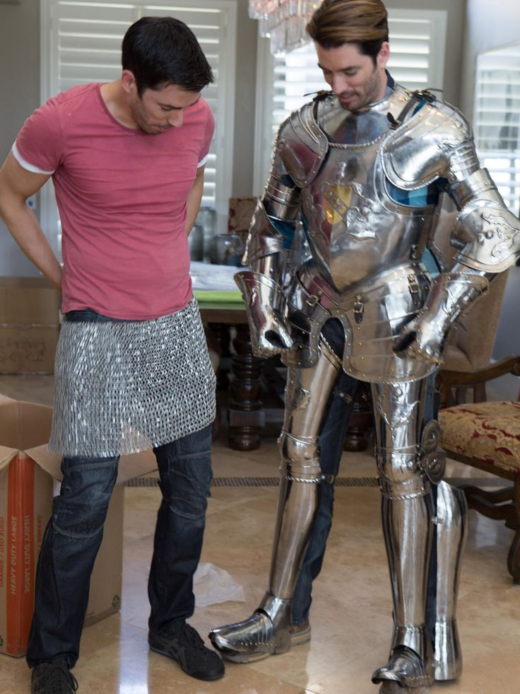 Drew Scott goofs around with a piece of armor while his brother Jonathan Scott tries on the entire suit.