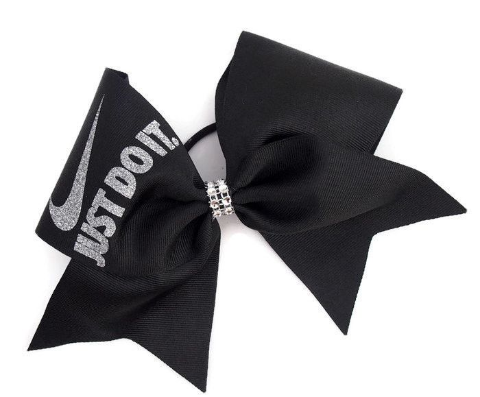 """This black cheer bow will be perfect for practice or competition. It is made with high quality US made 3"""" grosgrain ribbon. The swoosh and words are made with sparkly silver glitter vinyl. This has 1"""