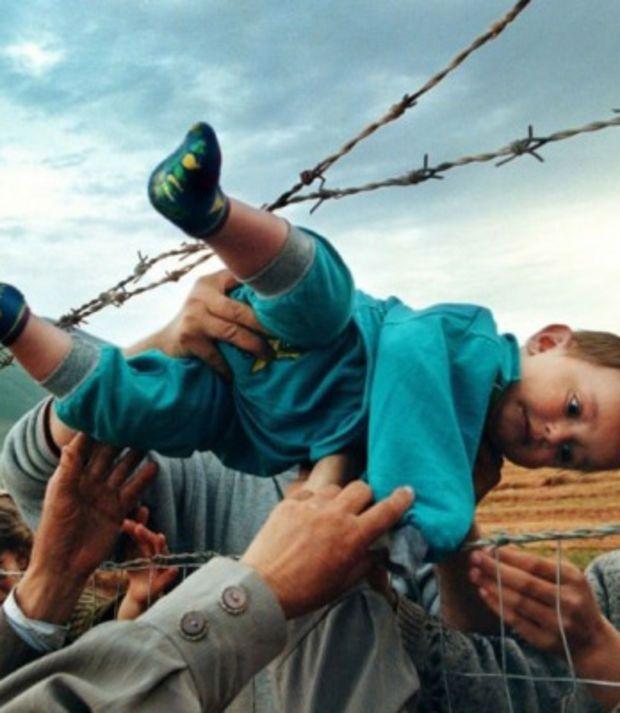 Un enfant est passé au dessus d'un grillage dans un camp de réfugiés au Kosovo afin qu'il retrouve ses grands-parents
