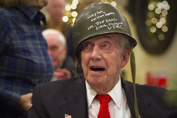 Pearl Harbor survivor William Keith wears an old service helmet signed by other survivors during a fundraiser event hosted by the World War Two Foundation to honor the 74th anniversary of the attack on Pearl Harbor at Port 305 in Marina Bay in Quincy on Monday December 7, 2015. Photo by Lauren Owens / for The Patriot Ledger