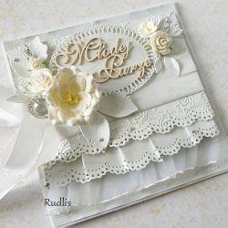 Romantyczna i wyjątkowa kartka z okazji ślubu. Wykonana z wykorzystaniem profesjonalnych materiałów. Ozdobiona tiulową falbanką, delikatnym wytłaczanym tłem, przeszywana maszynowo. Jako dodatek duże przestrzenne kwiaty, piękny ćwiek oraz drobne srebrne perełki.  Wymiar kartki ok 13x13 cm w komplecie z ozdobnym pudełkiem. Na życzenie Klienta mogę dodać imiona Młodej Pary na pudełku.